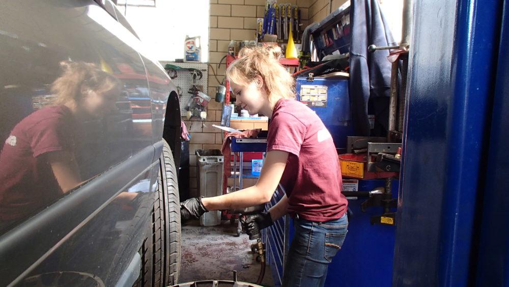 Female mechanic working on a car
